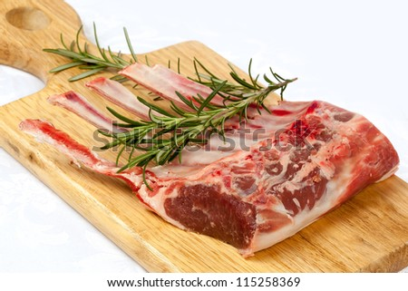 Rack of lamb with rosemary on a wooden board. - stock photo