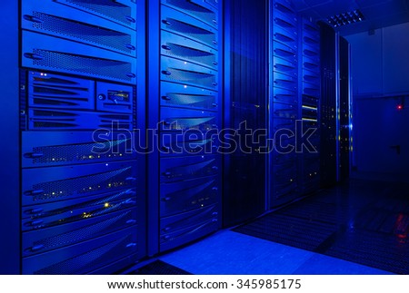 rack server hardware in the data center in blue light - stock photo