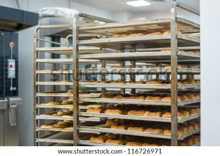 Rack trolley with baked bread in supermarket department - stock photo