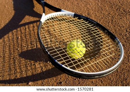 Racket and tennis ball on the tennis field, nice light, warm image