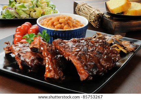Racks of barbecue ribs drenched in sauce with salad and cornbread - stock photo