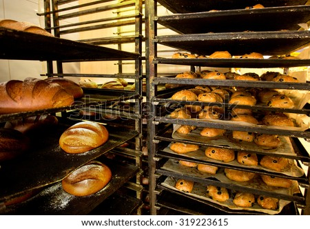 Racks of fresh buns with olives and bread from oven in Bakery
