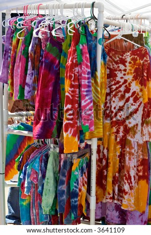 Racks of tie-dyed clothing for sale at an outdoor market in Cleveland Ohio. - stock photo