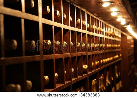 Racks with bottles in a dark wine cellar - stock photo