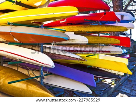Racks with storage of colorful canoes - stock photo