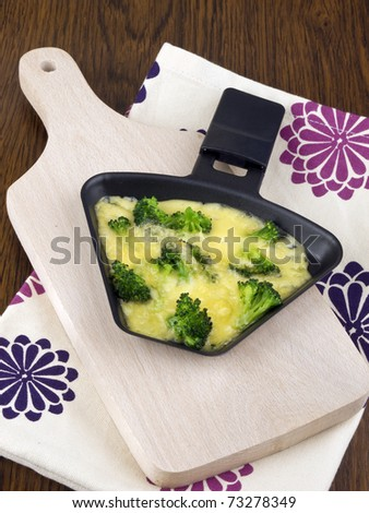 Raclette pan with edam cheese and broccoli on chopping board - stock photo