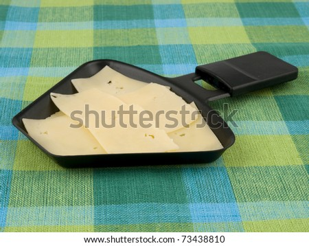 Raclette pan with edam cheese on colorful tablecloth - stock photo