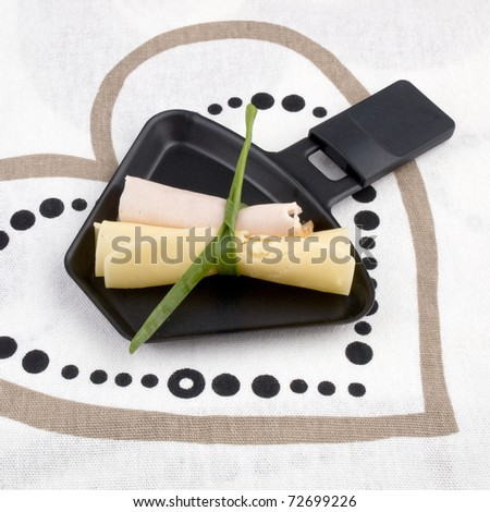 Raclette pan with rolled cheese and ham - stock photo
