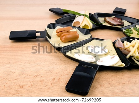 Raclette pans with edam cheese and ham, bacon, mushroom, spring onion, coctail sausages on wooden table - stock photo