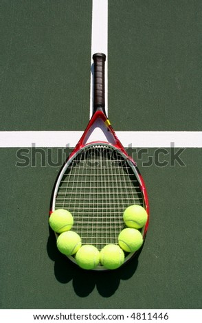 Racquet with balls on the court - stock photo