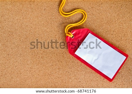 Rad plastic luggage tag isolated on cork board background - stock photo