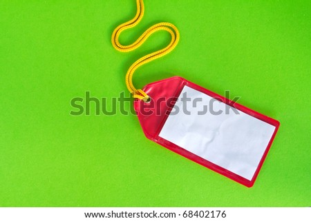 Rad plastic luggage tag isolated on green background - stock photo