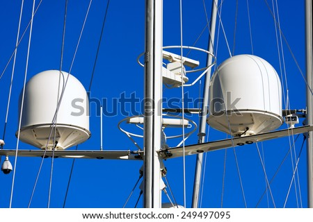 Radar and Communication Tower on a Yacht. Detail of luxury white yacht with security camera and navigation equipment, radar and antennas on blue sky - stock photo