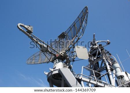 Radar on military ship against blue sky - stock photo