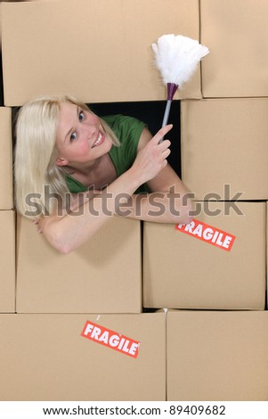 radiant blonde amid cardboard boxes holding feather duster