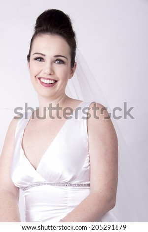 Radiant Brunette Bride smiling wearing a white bridal gown - stock photo