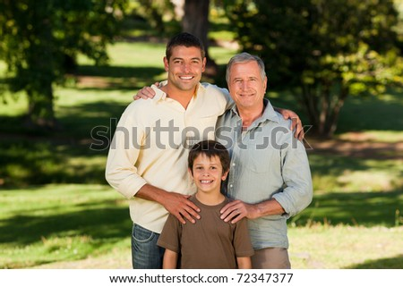 Radiant family looking at the camera in the park - stock photo