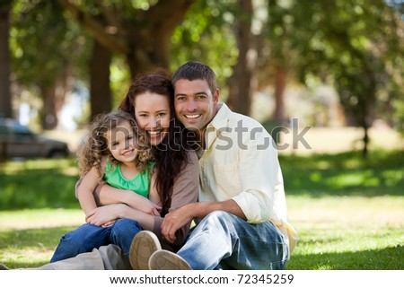 Radiant family sitting in the garden - stock photo