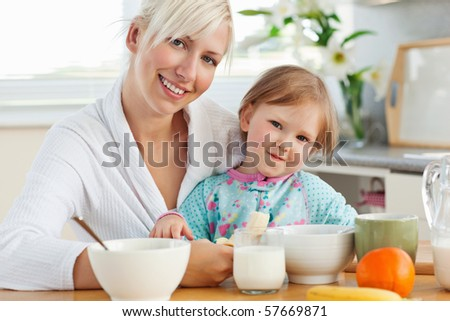 Radiant mother and daughter having breakfast in the kitchen