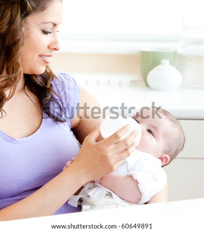 Radiant mother feeding her adorable son in the kitchen at home - stock photo