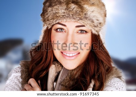 Radiant Winter Beauty. Beauty shot of a radiant smiling woman full of vitality and with a lovely complexion., against blue sky - stock photo