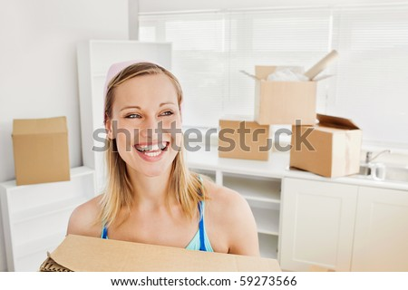Radiant woman holding boxes after moving - stock photo