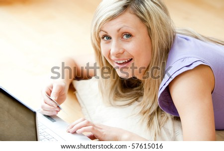 Radiant woman using a laptop lying on the floor holding a card