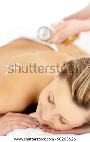Radiant young woman having a back massage with oil in a spa center