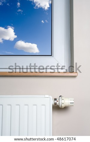 Radiator and blue sky in home interior, heater and thermostat - stock photo