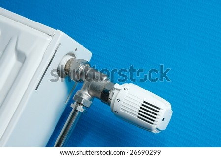 Radiator closeup with valve and blue wall - stock photo