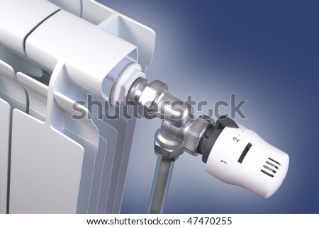 Radiator detail with thermostatic valve on blue background - stock photo