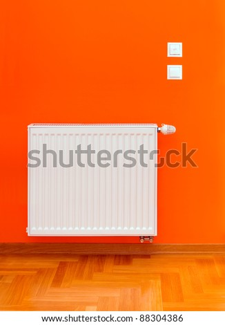 Radiator heater attached on the orange wall - stock photo