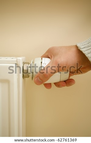 Radiator thermostat and hand - stock photo