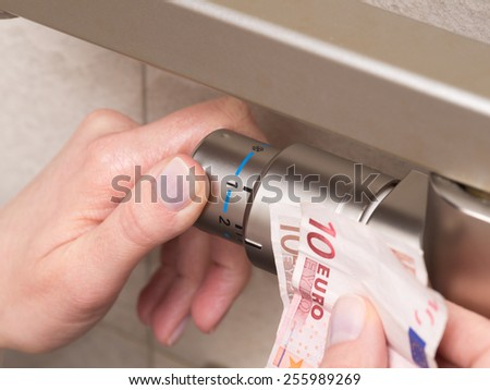Radiator thermostat and hand. Optimal setting of the thermostat valve. Radiator adjustment to save energy. Save energy and money concept - stock photo