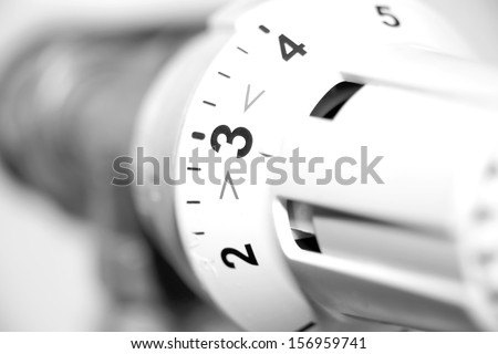 Radiator thermostat in black and white / heating cost - stock photo