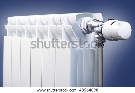 Radiator with thermostat valve isolated on blue gradient background - stock photo