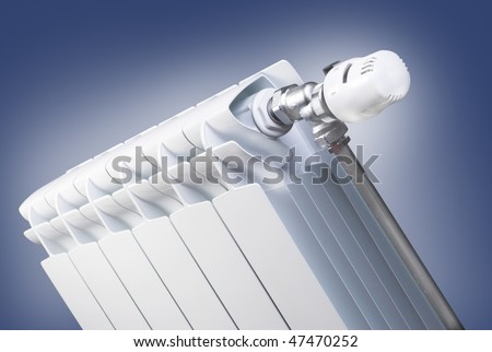 Radiator with thermostatic valve on blue background - stock photo