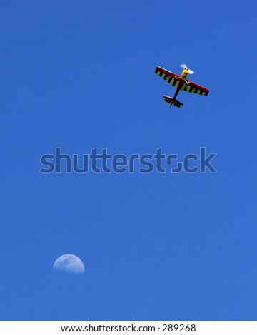 Radio-controlled airplane against blue sky with moon backdrop