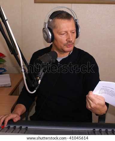 Radio DJ. Man with microphone and big headphone. - stock photo