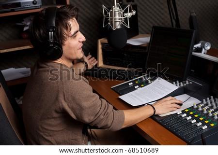 Radio DJ. Young man with microphone and headphone. - stock photo