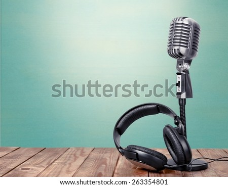 Radio. Microphone and headphones on table in front aquamarine wall background - stock photo