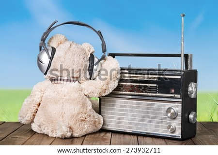 Radio. Retro toy Teddy Bear and radio receiver front mint green background - stock photo