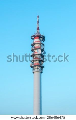 Radio tower with Communication dishes at dusk - stock photo