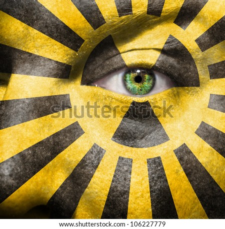 Radioactive sign and x-rays painted on a mans face to raise awareness for the nuclear debate - stock photo