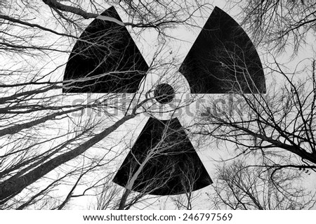 Radioactive symbol in the sky at dead trees. B&W - stock photo
