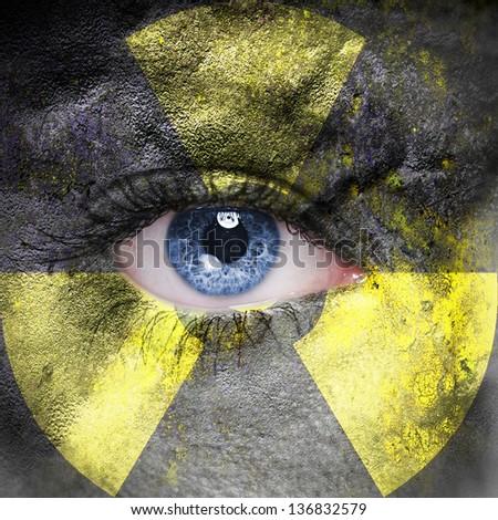 Radioactive symbol on human face - stock photo