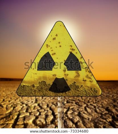 Radioactivity sigh over cracked land and sun - stock photo