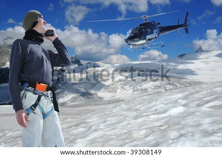 radioing for help on a walkie-talkie from a helicopter on a high glacier with the matterhorn in the background. He is equiped with harness and protective clothing and radio beacon around his waist
