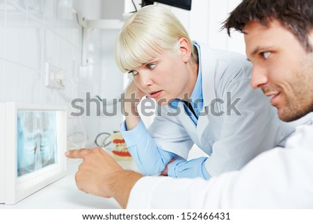 Radiologist and dentist examine together a panoramic radiograph of teeth