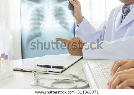 Radiologist examine image X-ray lungs and doctor are records data in lab at hospital. - stock photo